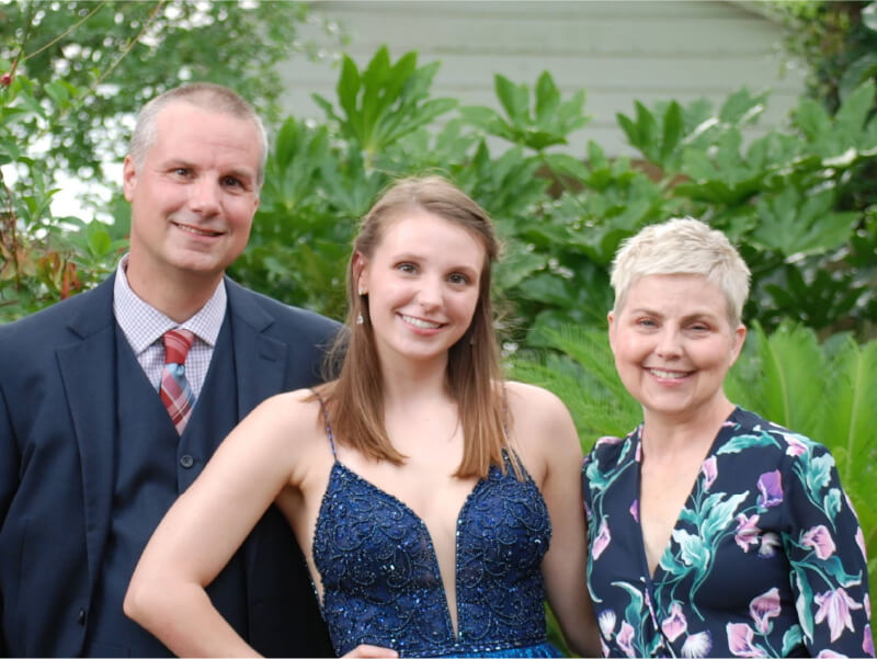 Kelly Draganov, double lung recipient, smiling with husband and daughter.