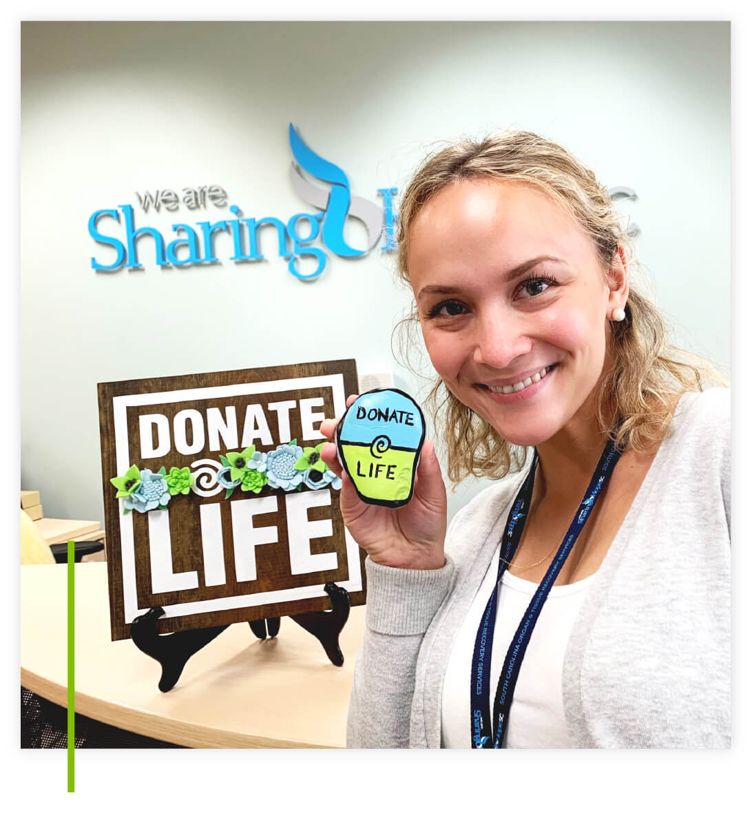We Are Sharing Hope SC employee smiling and holding at painted Donate Life decorative rock in the We Are We Are Sharing Hope SC office.