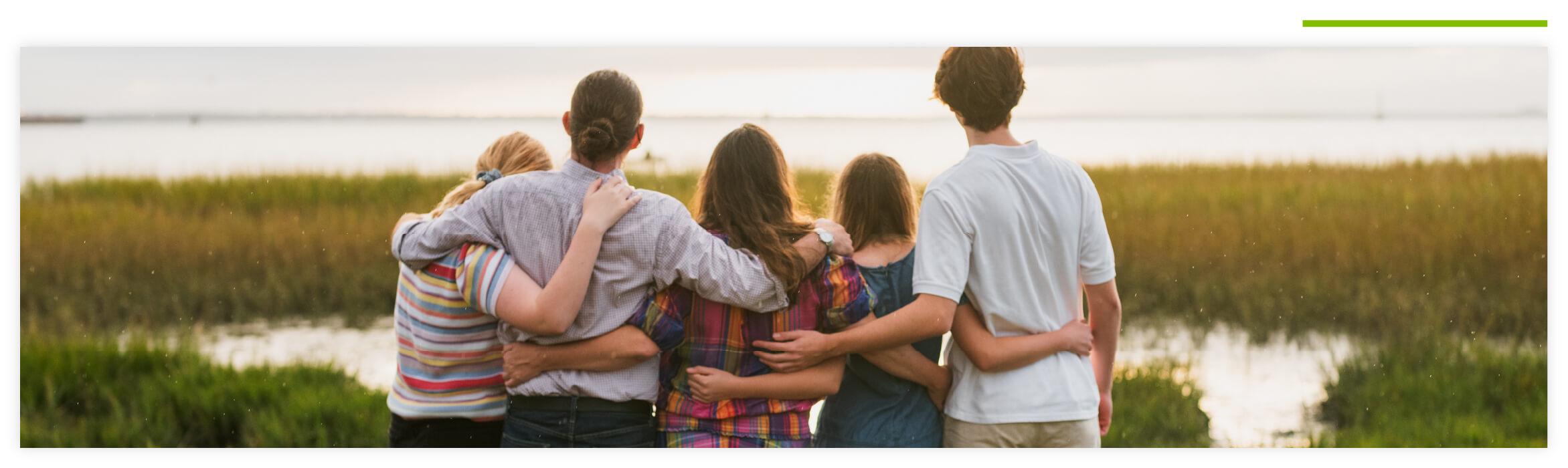 Group of men and women with their arms around each other's backs, facing the sunset outside at a lake.