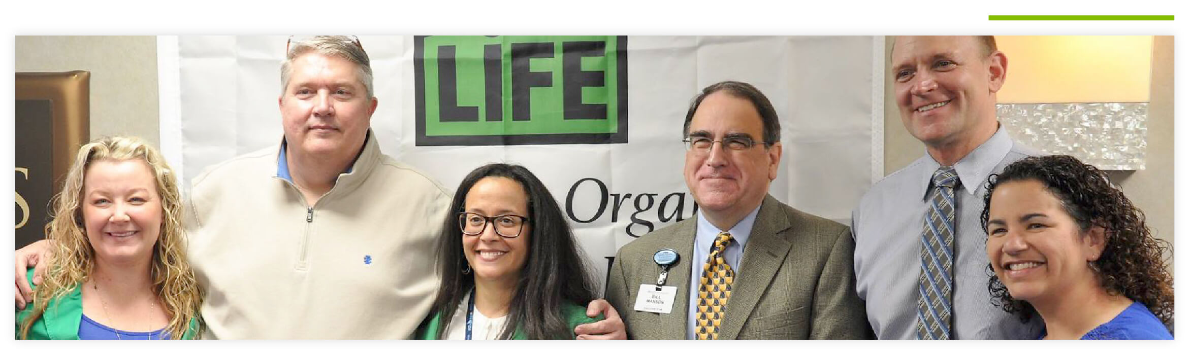 Group of six We Are Sharing Hope SC and Donate Life South Carolina employees smiling and standing in front of a Donate Life South Carolina banner.